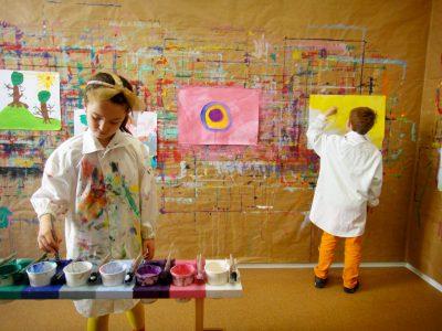 Kinder beim malen an der Wand